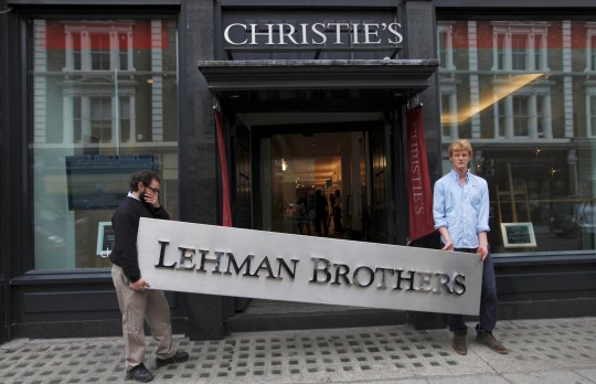 FILE PHOTO: Christie's employees pose with a Lehman Brothers sign at Christie's in central London September 24, 2010. REUTERS/Andrew Winning/File Photo