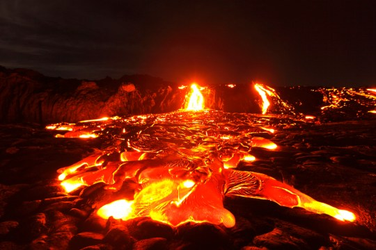 The lava flow goes down a cliff and advances to the ocean at night.
