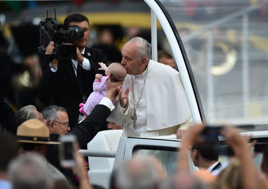 Pope Francis kisses an infant en route to Independence Hall in Philadelphia on September 26, 2015. AFP PHOTO / VINCENZO PINTO (Photo credit should read VINCENZO PINTO/AFP/Getty Images)