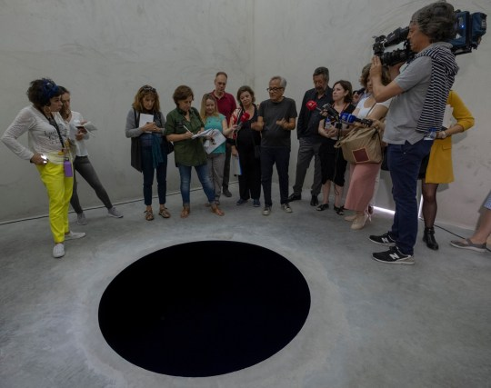 "PORTO, PORTUGAL - JULY 06: Indian artist Anish Kapoor talks to journalists inside the cube structure of Descent into Limbo during the presentation to the press of his exhibition ""Anish Kapoor: Works, Thoughts, Experiments"" in Serralves Museum and Park on July 06, 2018 in Porto, Portugal. The exhibition presents a selection of outdoor works that are representative of Kapoors sculptural language, its choice and siting of sculptures in the Park of Serralves carefully considered by the artist so as to create an itinerary through time, space, perception and meaning. The central exhibition space of Serralves Museum hosts 56 models of realized and unrealized projects conceived by the artist over the past 40 years showing the intimate scale of the artists studio as a space of thinking and experimentation. ""Anish Kapoor: Works, Thoughts, Experiments"" will be opened to the public until January 09, 2019. (Photo by Horacio Villalobos - Corbis/Corbis via Getty Images)"