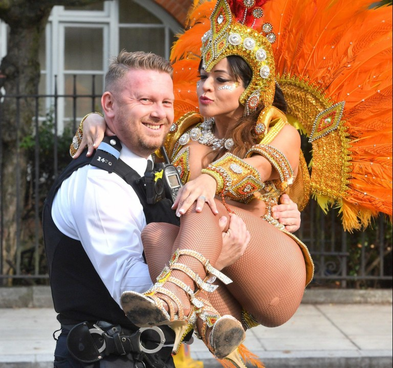 PC Gary Hitchman poses with Brazilian dancer Juliana Campos as she prepares to take part in the Notting Hill Carnival in west London. PRESS ASSOCIATION Photo. Picture date: Monday August 27, 2018. Photo credit should read: John Stillwell/PA Wire