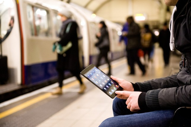 LONDON, UNITED KINGDOM - JANUARY 14: A man using an Apple iPad Mini tablet computer whilst waiting for an underground train on January 14, 2013. (Photo by Will Ireland/Future Publishing via Getty Images)