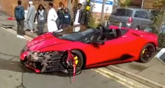 A badly damaged Lamborghini Huracan attracts a crowd in a residential street, after a driver lost control of the GBP180,000 vehicle in Small Heath, Birmingham, Saturday 25th August, 2018. TALK about a Lamb to the slaughter! Footage has emerged of a LAMBORGHINI worth ??180,000 after it crashed into a residential street in Birmingham on Saturday 25th August ?? to the shock and bemusement of onlookers. The driver lost control of the supercar ?? which is capable of doing as he accelerated and smashed it into an electrical box on Golden Hilock Road in Small Heath. In the video, crowds of stunned residents gather to see the bright red Lamborghini Huracan ?? capable of doing 201mph ?? smashed to bits. The entire front end of the Italian supercar is torn away and the vehicle would have likely been written off. In the clip, neighbours on Golden Hillcock Road stare and gawp at the wrecked Lambo ?? which had been worth more than most of their houses. One resident can be heard saying ??Look like somebody??s house deposit is gone!?? ... SEE COPY AND VIDEO ... PIC BY NEWS DOG MEDIA ... 0121 517 0019