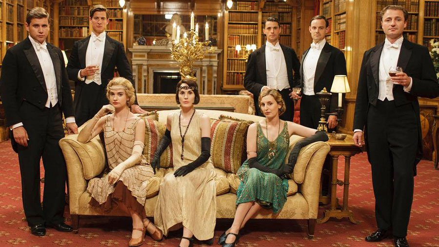 Television programme: Downton Abbey - Series 5. Lily James (seated, left)as Lady Rose. Champagne dress supplied by Starry Starry Night in Glasgow