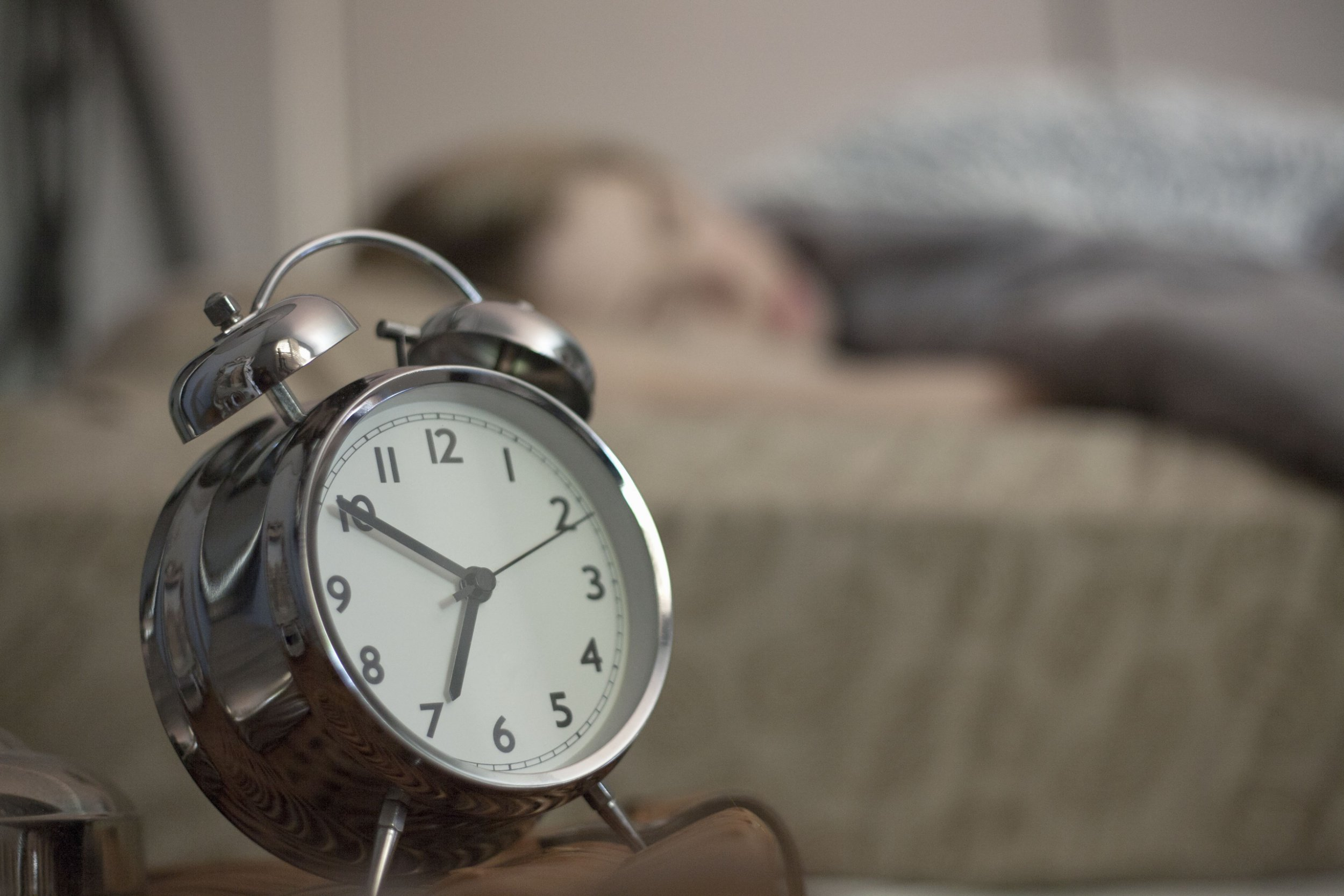 MINIMUM USAGE FEE ?35. Please call Rex Features on 020 7278 7294 with any queries. Mandatory Credit: Photo by Image Source/REX/Shutterstock (4787666a) MODEL RELEASED, Close up of alarm clock, woman in background. VARIOUS