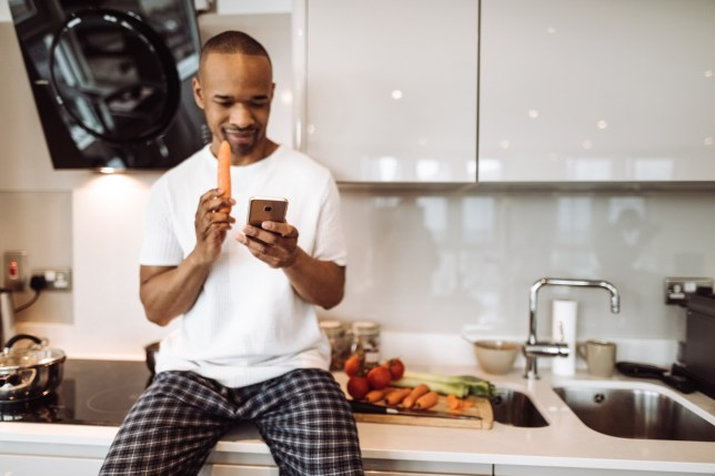 man using the phone in the kitchen and eating a carrot