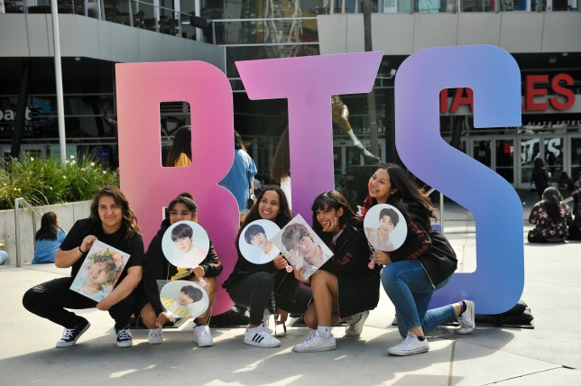 "LOS ANGELES, CA - SEPTEMBER 05: (L-R) Fans Diana Cruz, 18, Cici Diaz, 18, Madison Oliveras, 18, Yosselin Pineda 18, and Kimberly Jafri, 17, pose in front of a BTS sign while they wait for the BTS concert at the Staples Center as part of the ""Love Yourself"" North American Tour on September 5, 2018 in Los Angeles, California. (Photo by Rachel Luna/Getty Images)"