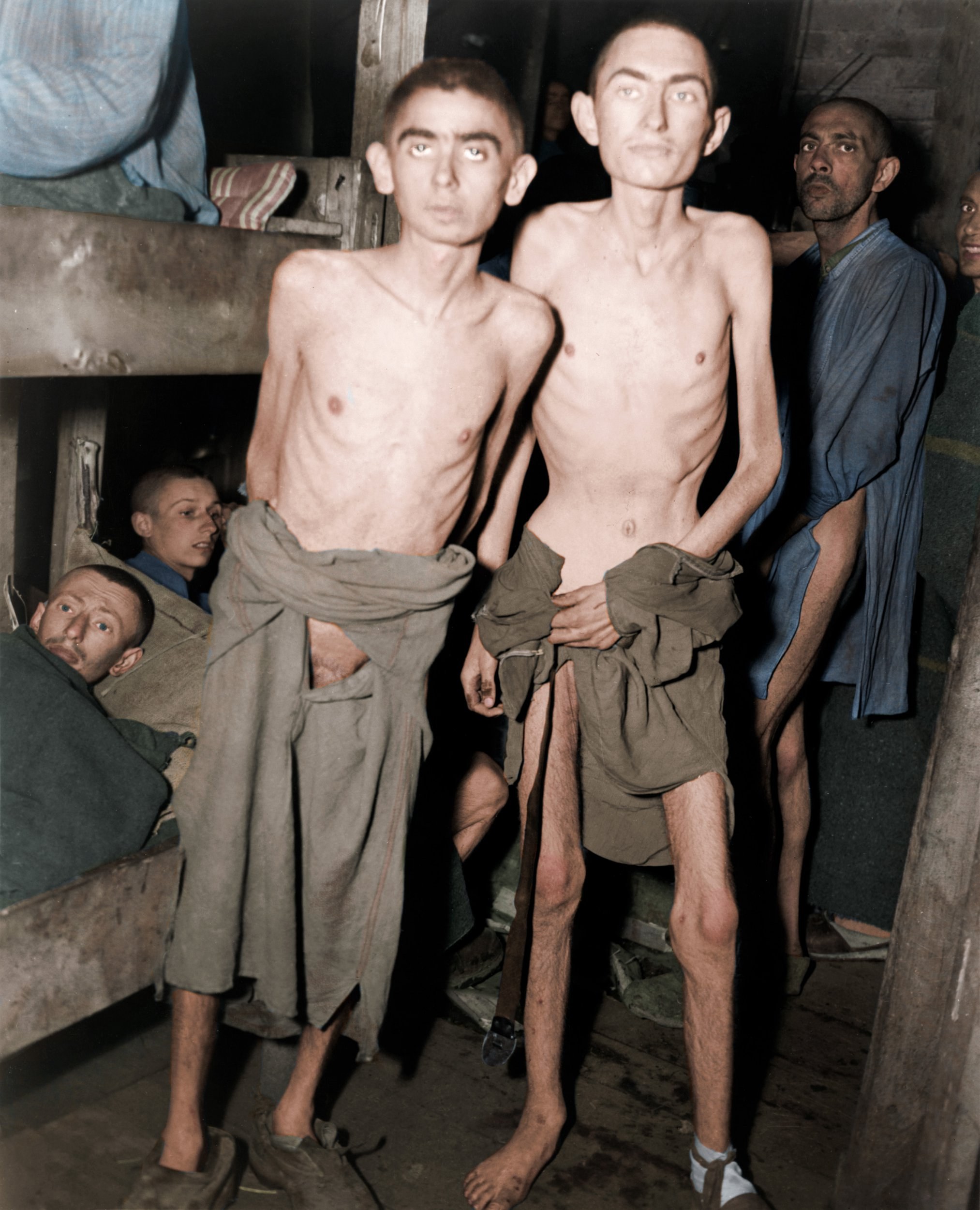 Inmates of the Ampfing subcamps in Germany after having been liberated by U.S. Third Army troops, Germany, 4 May 1945. Subcamps are a lesser known aspect of the concentration camp system in Nazi Germany. Prisoners in the Waldlager V and VI, located near the town of Ampfing, were housed in barracks partially submerged in the ground with soil-covered roofs designed to camouflage the structures from Allied aerial reconnaissance. THE HEARTBREAKING horrors of the Holocaust have been brought into light again thanks to a series of colourised images. Striking shots show Senator Alben W. Barkley, member of a committee investigating Nazi atrocities, looking at a pile of bodies at Buchenwald concentration camp; Jews being executed by German army mobile killing units, the Einsatzgruppen, after they had dug their own graves; and starving children asking for alms in the Warsaw Ghetto. Other horrifying images show thousands of wedding rings the Nazis removed from their victims to salvage the gold, prisoner no.40472 of the Auschwitz concentration camp who was identified as Michal Loborski and members of the 42nd Rainbow Division, 7th US Army uncovering a wagon transporting some of the horrors of Dachau. The original black and white photographs were colourised by Joel Bellviure (17) who lives between Palma, Mallorca and Barcelona, Spain. Joel Bellviure / mediadrumworld.com