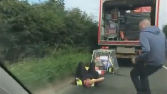 SHOCKING video shows the moment a van driver is crushed beneath a cage of food and drink that falls off the back of his vehicle. The footage shows the driver lying stunned in the road with blood coming from a head injury. The back door of the van is thought to have sprung open mid-journey and the driver stopped after he was alerted by other motorists. Jack Myserscough filmed the incident in Bolton, Greater Manchester, on Friday, after stopping to warn the driver, believed to be David Simmons. Jack, a driver with 1SR Prestige Car Specialists, can be heard beeping his horn for several seconds until the vehicle stops.