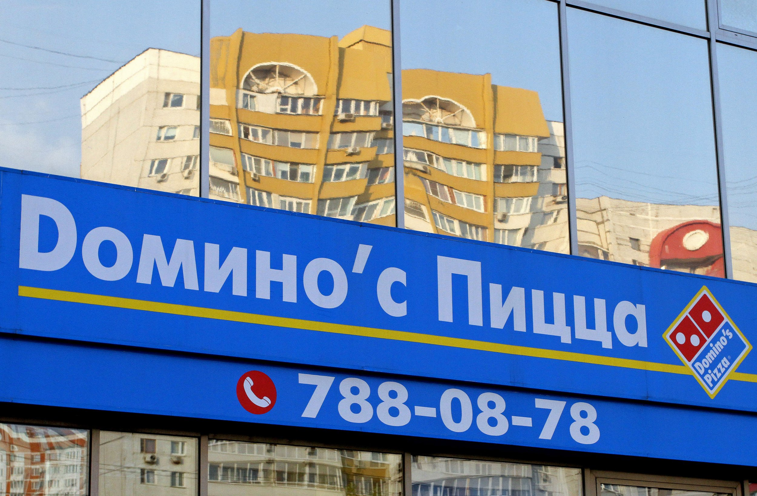 A Russian logo sits on display outside a Domino's Pizza Inc. fast food store in Moscow, Russia, on Tuesday, Aug. 16, 2011. Domino's, which has 4,900 stores in the U.S. and 4,400 international locations, will open as many as 300 stores a year over the long-term, with most being in overseas markets. Photographer: Andrey Rudakov/Bloomberg via Getty Images