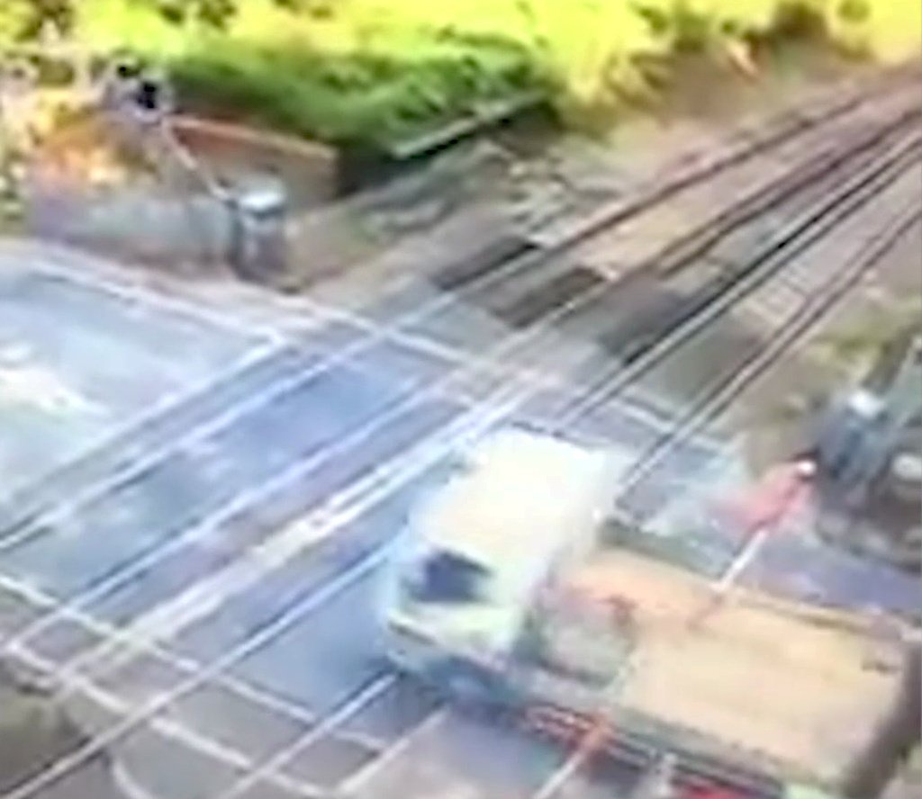 "This lorry driver who ploughed through barriers at a level crossing is being hunted by police. See National News story NNCROSSING; CCTV footage caught the moment the flat-bed smashed the gates and cause hours of train and road delays near Battle in East Sussex. British Transport Police appealed for witnesses as the driver remains on the run following the crash at 1pm last Friday. A spokesman said: ""Police is aware of a collision that took place on a level crossing just after 1pm Friday, September 7, near Battle, East Sussex."