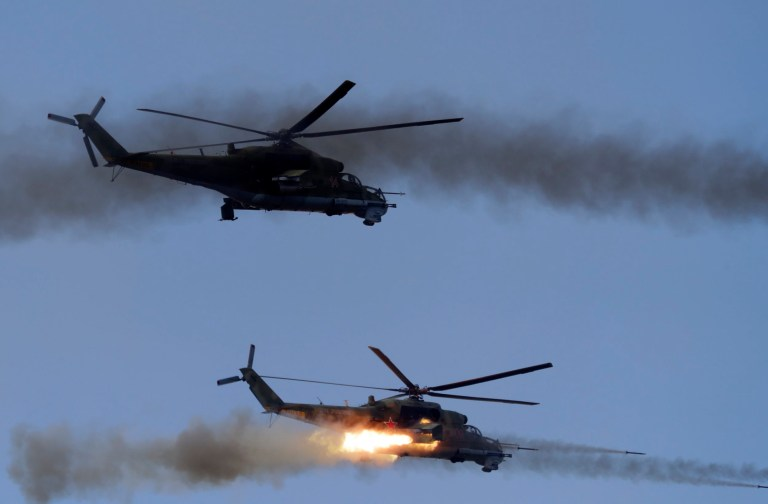 "Military helicopters fire over the training ground ""Telemba"", about 80 kilometers (50 miles) north of the city of Chita during the military exercises Vostok 2018 in Eastern Siberia, Russia, Thursday, Sept. 13, 2018. Russian President Vladimir Putin on Thursday inspected war games in eastern Siberia which have been billed as the biggest Russia has ever had. (AP Photo/Sergei Grits)"