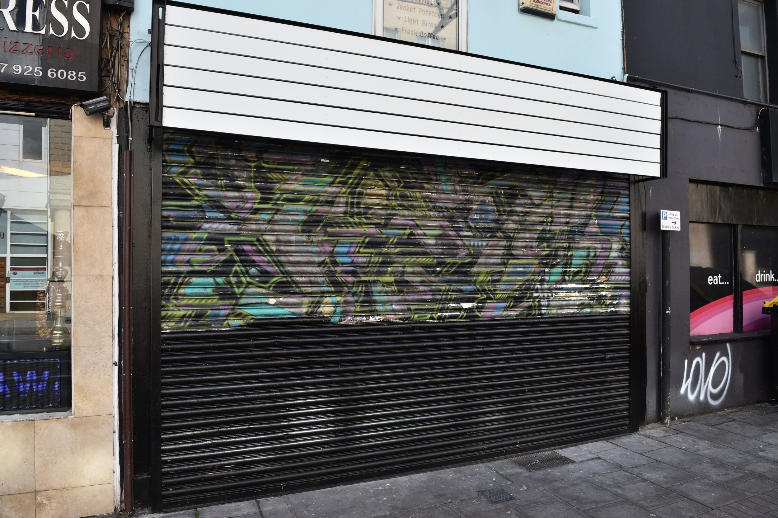 A Banksy mural on the shopfront shutters on Park Row, Bristol has been accidentally painted over in black by the new owners of the shop during renovations. PRESS ASSOCIATION Photo. Picture date: Thursday September 13, 2018. Photo credit should read: Ben Birchall/PA Wire
