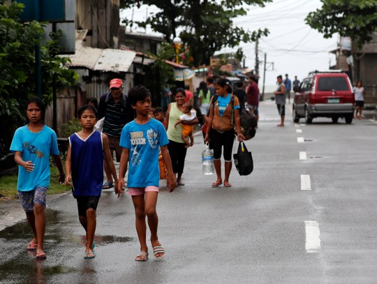 epa07019920 Filipino villagers with their belongings head to an evacuation center in the town of Aparri, ahead of Typhoon Mangkhut landfall in the region, in Cagayan province, Philippines, 14 September 2018. Philippines braced for the arrival of Typhoon Mangkhut, ranked as the most powerful storm of the year to enter the Philippines, as it was expected to hit the northern island of Luzon. EPA/FRANCIS R. MALASIG