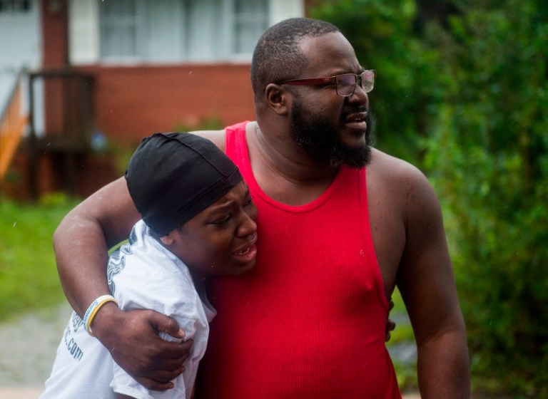 TOPSHOT - A father and daughter learn that friends were injured in a house that a tree fell on during landfall of Hurricane Florence, in Wilmington, North Carolina on September 14, 2018. - Florence smashed into the US East Coast Friday with howling winds, torrential rains and life-threatening storm surges as emergency crews scrambled to rescue hundreds of people stranded in their homes by flood waters. Forecasters warned of catastrophic flooding and other mayhem from the monster storm, which is only Category 1 but physically sprawling and dangerous. (Photo by ANDREW CABALLERO-REYNOLDS / AFP)ANDREW CABALLERO-REYNOLDS/AFP/Getty Images