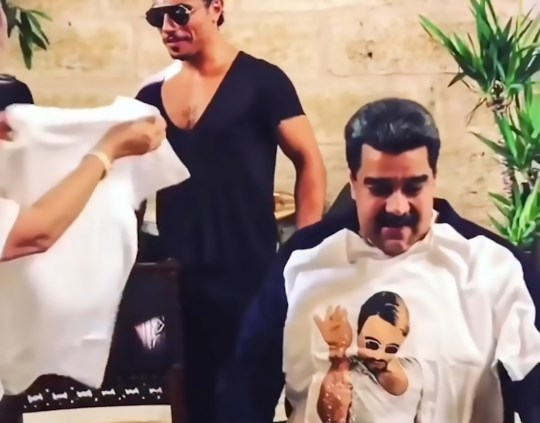 """Pic Shows: Nicolas Maduro wearing a shirt of 'Salt Bae'; Controversial Venezuelan President Nicolas Maduro and his wife have been spotted enjoying a luxury meal served personally by non other than celebrity chef Salt Bae while his country continues to suffer economic ruin. The footage was taken at Salt Bae's luxurious restaurant in Istanbul, Turkey, where the top chef, real name Nusret Gokce, has made an art of preparing, salting, and cutting fine cuts of meat. The restaurant has become popular with the wealthy and famous including visitors such as Cristiano Ronaldo, Leonardo DiCaprio, Justin Bieber, and Diego Maradona. The Turkish restaurateur has become a global food star and his latest stunt was to share with his 15.5 million online fans on Instagram a clip of himself preparing his signature dish with the comment """"24 carat gold steak!"""" having coated the food in gold. Gokce famously wears shades and and has donned black rubber gloves since becoming famous for hygiene reasons, as he rolls salt down his forearms, and off his elbow onto succulent cuts of prime meat. The chef himself posted the recent footage displaying his highly original preparation techniques, commenting on how much President Maduro and his wife Cilia Flores had enjoyed their luxury meal. He removed the clip shortly after but by then the video had gone viral. Images of Maduro smoking a cigar and watching with anticipation as one of the world???s top chefs personally prepares choice cuts of meat caused indignation in Venezuela, which despite being a major oil producer, is in the throes of a sustained economic crisis. A contented looking Maduro can be heard commenting: """"This is a once-in-a-lifetime experience."""" After the meal, he gives the chef a hug and invites him to visit him in Caracas. As he leaves the restaurant, he is flanked by heavy security wearing Turkish police insignia. It is not clear exactly when the footage was taken, although it is believed to have been filmed during a stop"""