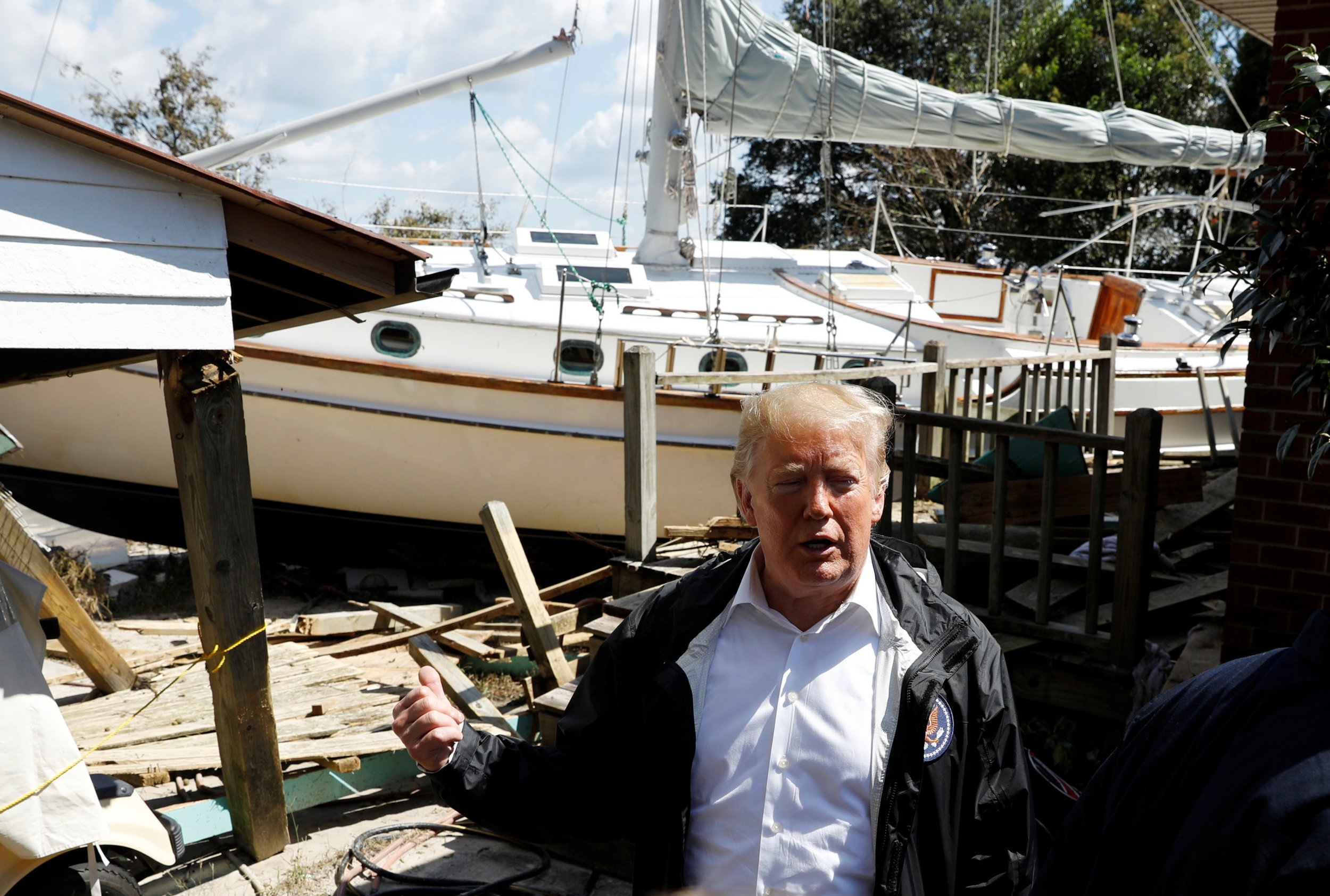 U.S. President Donald Trump stands in front of a damaged sailboat while touring Hurricane Florence damage in New Bern, North Carolina, U.S., September 19, 2018. REUTERS/Kevin Lamarque