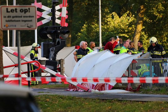 "Rescue workers tend to victims of a collision on a railway line, next to a sign in Dutch, left, reading ""Warning, in this area cargo bikes are being used"" in Oss, Netherlands, Thursday Sept. 20, 2018. Dutch police say that four children have been killed and two people seriously injured in a collision between a train and a cargo bike. (AP Photo/Charles Mallo) NOT FOR USE IN THE NETHERLANDS, NO SALES, MANDATORY CREDIT"