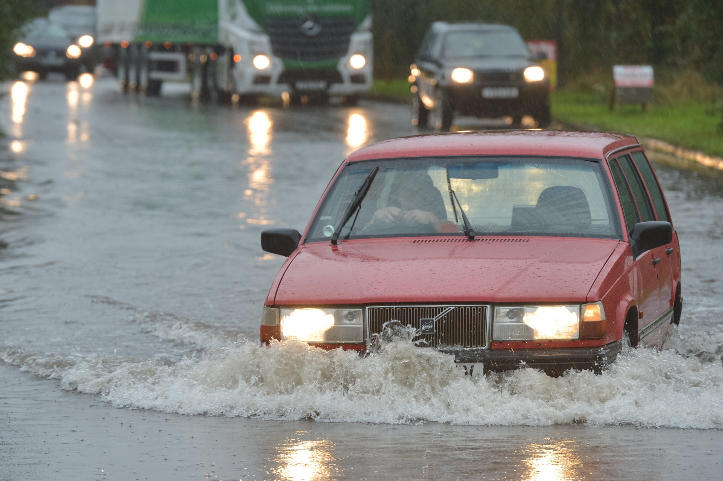 An old Volvo ploughs through a flooded road, the only access to Skippingdale Retail Park in Scunthorpe, North Lincs., which is now home to a number of stranded drivers unwilling to take the risk, September 20 2018.
