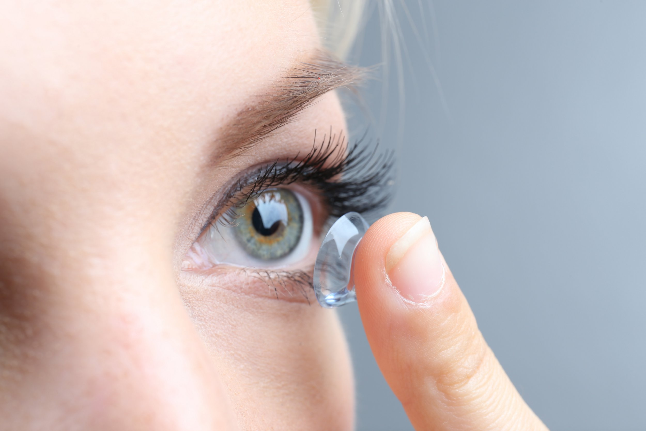 Medicine and vision concept - young woman with contact lens, close up; Shutterstock ID 226192345; Purchase Order: -