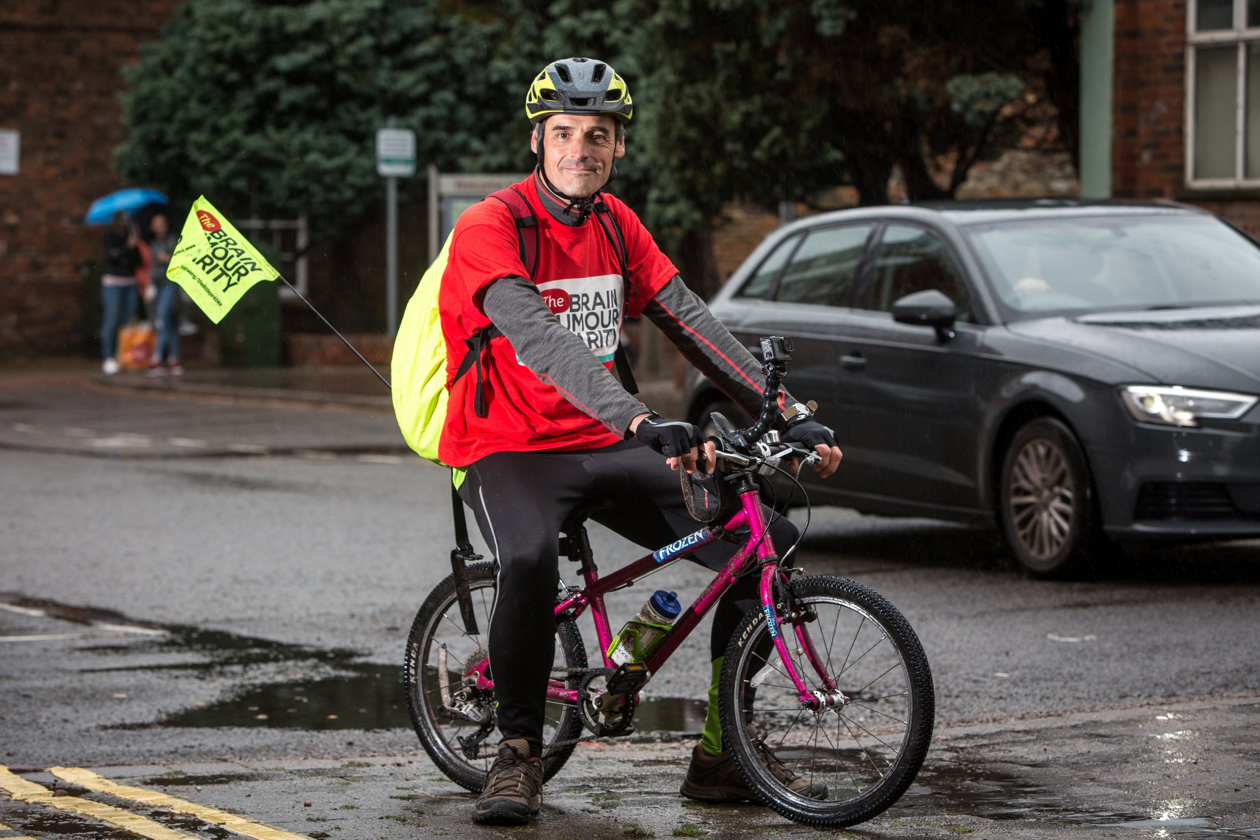 Peter Williams who lost his seven year old daughter Ellie to cancer rides her tiny pink bike on a 200 mile route from Bristol to Land???s End. See SWNS story SWBIKE; A devoted dad is riding 200 miles on his late daughter's tiny bike to raise money for charity. Peter Williams has set off on his challenge in memory of seven-year-old Ellie who died from a brain tumour three years ago. He will now spend around a week pedaling the undersized bike from Bristol to Land's End in support of the Brain Tumour Charity. Peter, from Penzance, Cornwall, who is 6ft, left from the Bristol Children's Hospital.