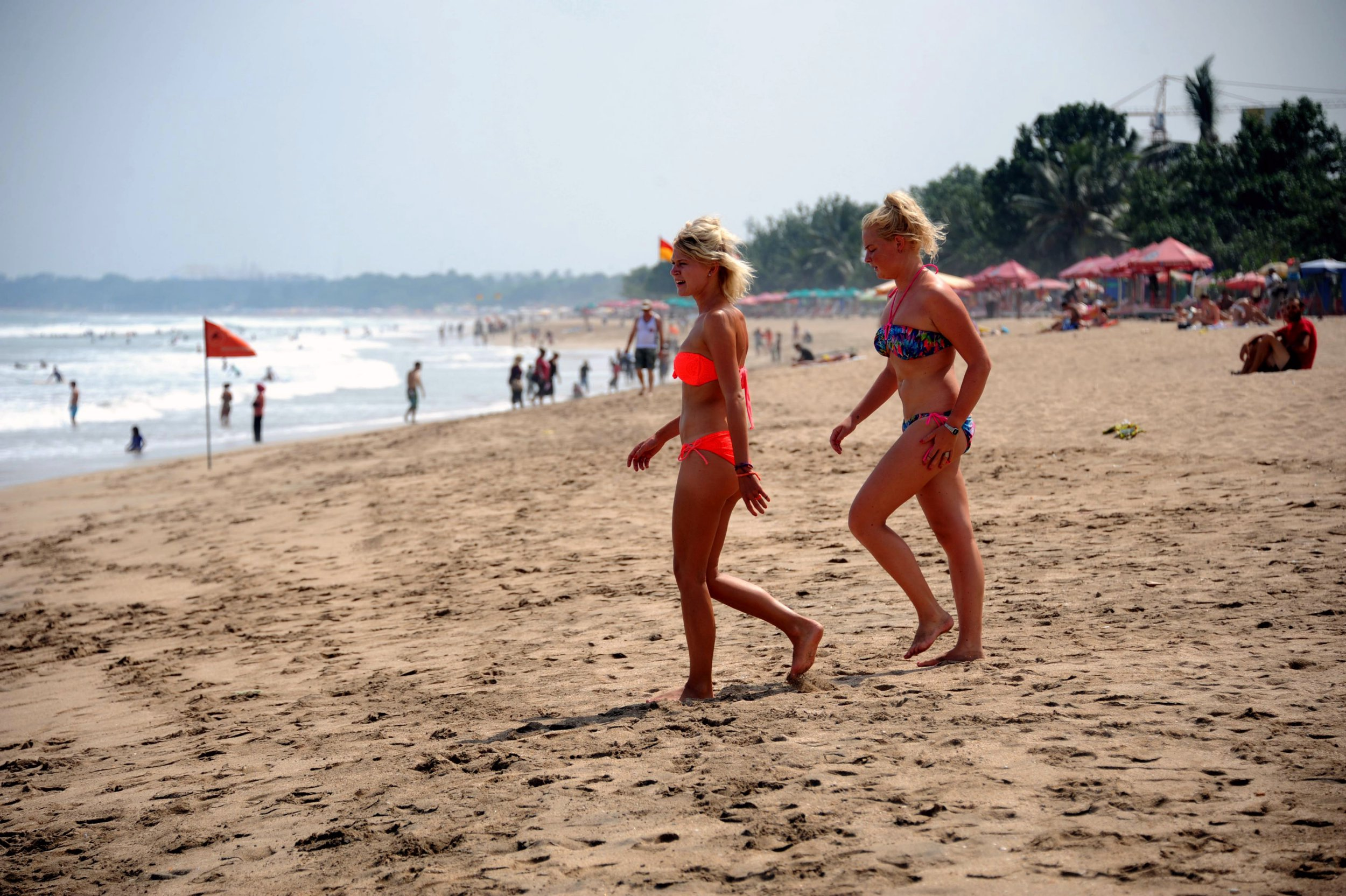 Tourists wearing bikinis walk along Kuta beach in Bali on June 6, 2013. Contestants at this year's Miss World beauty pageant will not wear bikinis in the parade in a bid to avoid causing offence in Muslim-majority Indonesia, organisers said on June 5, 2013. AFP PHOTO/SONNY TUMBELAKA (Photo credit should read SONNY TUMBELAKA/AFP/Getty Images)