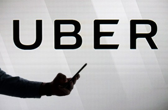A man checks his smartphone whilst standing against an illuminated screen bearing the Uber Technologies Inc. logo in this arranged photograph in London, U.K., on Tuesday, June 26, 2018. Uber won an 15-month probationary license to operate in London after convincing a judge and regulators that the ride-sharing service had shaken off its gung-ho attitude of the past. Photographer: Chris Ratcliffe/Bloomberg via Getty Images