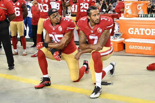 Colin Kaepernick #7 and Eric Reid #35 of the San Francisco 49ers kneel in protest during the national anthem prior to playing the Los Angeles Rams in their NFL game at Levi's Stadium