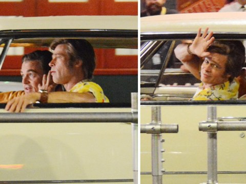 Brad Pitt gives us a wave as he takes Leonardo DiCaprio for a spin on set