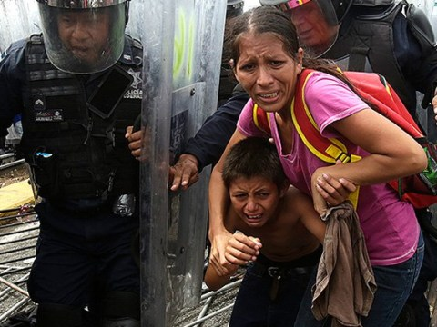 Desperate Honduran migrants push down border fence to get into Mexico