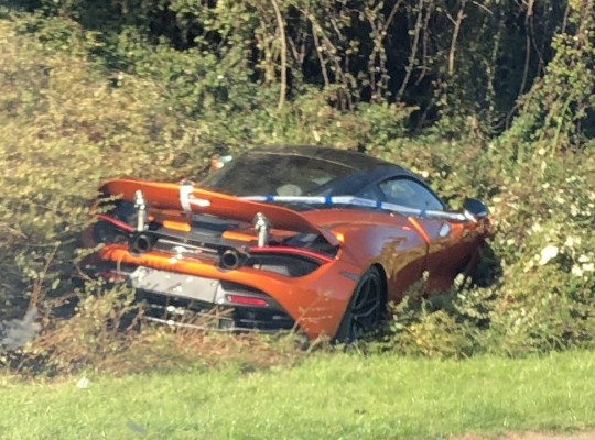 The crashed McLaren 720s left stranded in a hedgerow alongside a dual carriageway in Bradley Stoke, Bristol. See SWNS copy SWMCLAREN: A McLaren super car worth up to ?250,000 has been caught on camera buried in bushes on a busy roundabout. Video footage shows the orange McLaren 720s left stranded in a hedgerow alongside a dual carriageway in Bradley Stoke, Bristol. With a top speed of 210mph and boasting a huge 710 horsepower, the luxury super car is believed to have crashed after coming off the road yesterday afternoon.