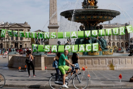 """A man rides a bicycle in front of a fountain bearing the sign """"let's put the car back in its place"""" as he enjoys a vehicle-free day in Paris, on September 16, 2018. - Europe should hold an annual car-free day in a bid to ease air pollution, the mayors of Paris and Brussels said on September 15, 2018 on the eve of a vehicle-free day in their cities. (Photo by FRANCOIS GUILLOT / AFP) (Photo credit should read FRANCOIS GUILLOT/AFP/Getty Images)"""