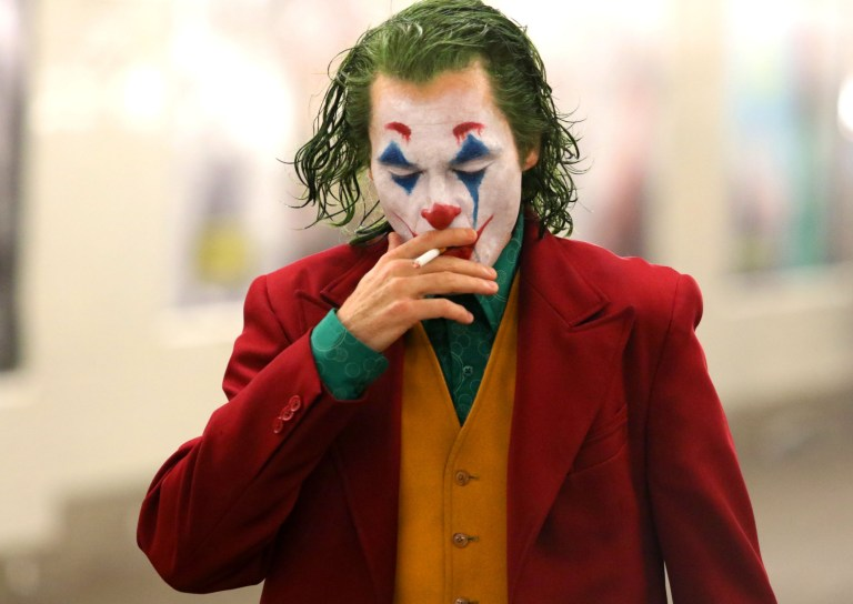 """Joaquin Phoenix is seen up close and personal and looking very menacing as the Clown Prince of Crime in full Joker make-up and costume as he shot dramatic scenes while smoking a cigarette and walking past several Gotham Police officers who were on hot pursuit for the scene. """"JOKER"""" filming took place at an underground Subway train station in Brooklyn. Pictured: Joaquin Phoenix Ref: SPL5031570 081018 NON-EXCLUSIVE Picture by: SplashNews.com Splash News and Pictures Los Angeles: 310-821-2666 New York: 212-619-2666 London: 0207 644 7656 Milan: +39 02 4399 8577 Sydney: +61 02 9240 7700 photodesk@splashnews.com World Rights,"""