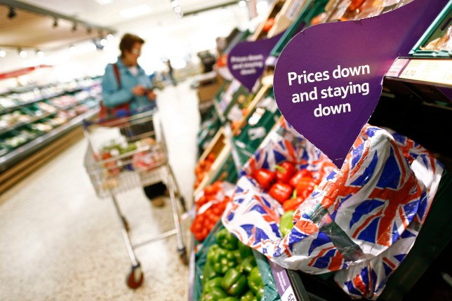 """A customer shops for fruit and vegetable goods near a sign that reads 'Prices down and staying down' inside a Tesco Extra Supermarket, operated by Tesco Plc, in London, U.K., on Tuesday, July 1, 2014. Tesco Chief Executive Officer Philip Clarke asked shareholders last week for more time to complete """"radical"""" changes, from altering shop formats to lowering prices. Photographer: Simon Dawson/Bloomberg via Getty Images"""