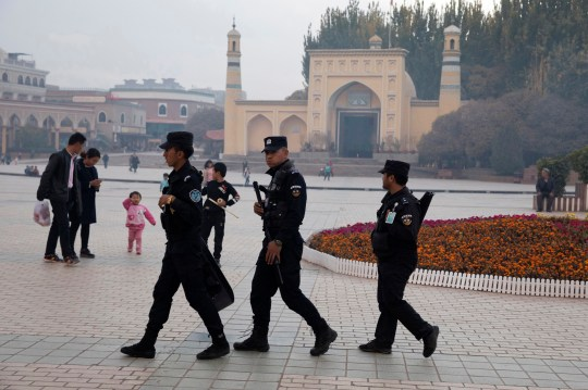 "FILE - In this Nov. 4, 2017 file photo, Uighur security personnel patrol near the Id Kah Mosque in Kashgar in western China's Xinjiang region. China's northwestern region of Xinjiang has revised legislation to allow the detention of suspected extremists in ""education and training centers."" The revisions come amid rising international concern over a harsh crackdown in Xinjiang that has led to as many as 1 million of China's Uighurs and other Muslim minorities being held in internment camps. (AP Photo/Ng Han Guan, File)"