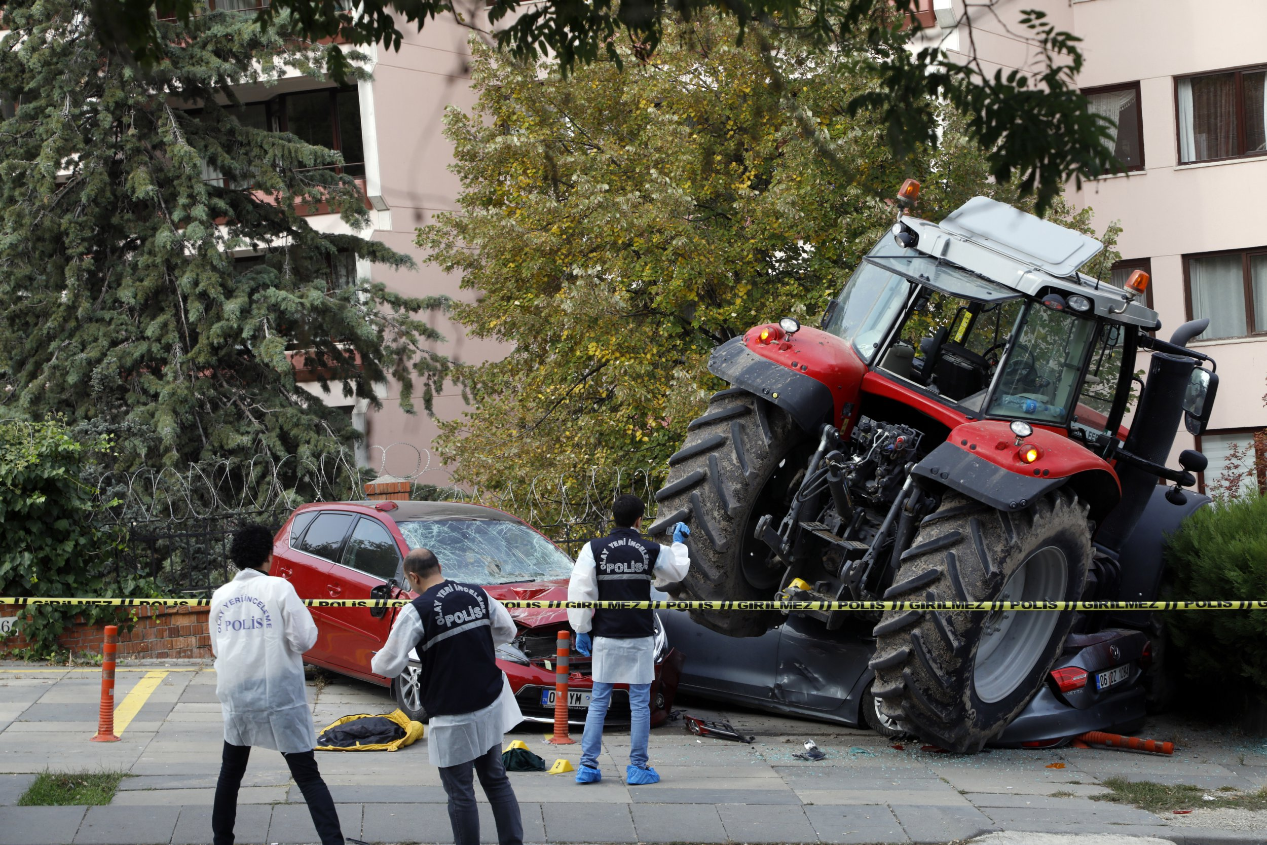 Forensic officers work at the scene after a tractor crashed into cars outside a residence, in Ankara, Turkey, Tuesday, Oct. 16, 2018. Police on Tuesday opened fire on a tractor that drove past parliament, other government buildings and embassies on a main boulevard, hitting cars along the way and ignoring calls to stop. The driver, who was shot in the leg, later told police he planned a protest outside the Israeli embassy, the state-run news agency reported. (AP Photo/Burhan Ozbilici)