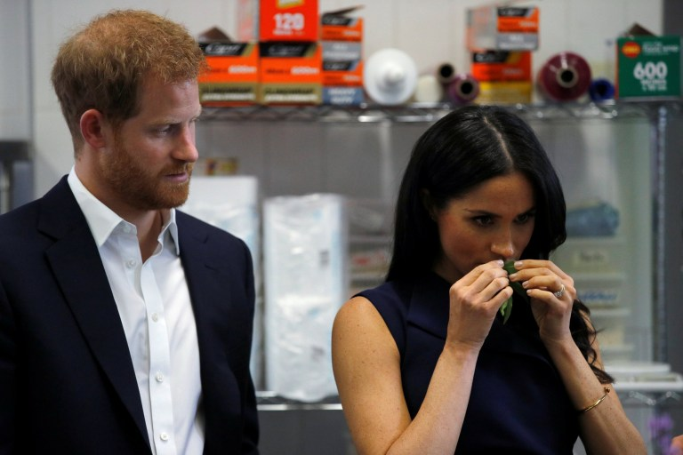 Britain's Prince Harry looks on as his wife, Meghan, Duchess of Sussex, smells traditional native Australian ingredients during a visit to Mission Australia social enterprise restaurant Charcoal Lane in Melbourne, Australia October 18, 2018. REUTERS/Phil Noble/Pool