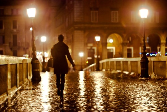A lonely woman walking by night in Ponte Sisto