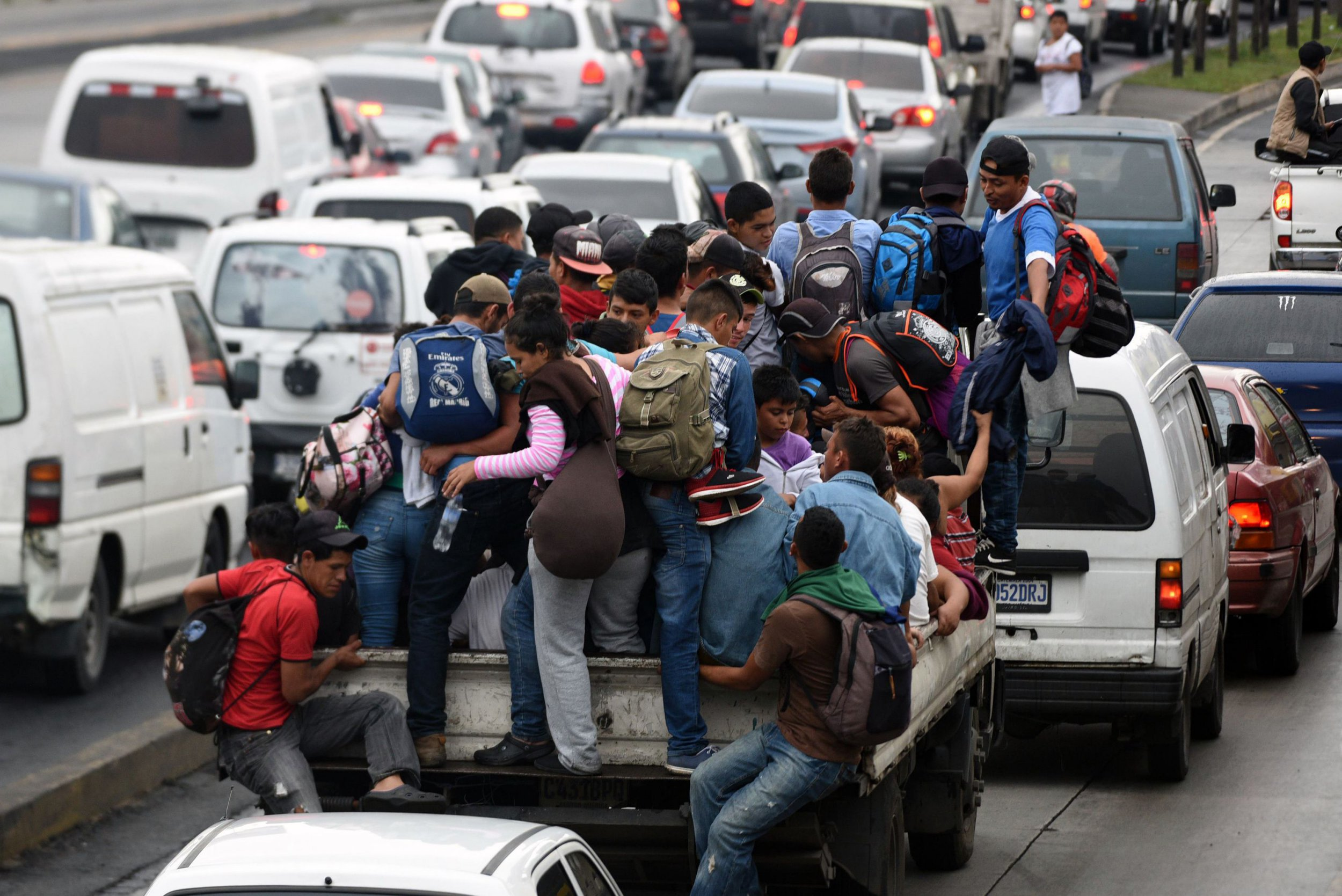"Honduran migrants aboard vehicles head in a caravan to the United States, in Guatemala City, on October 18, 2018. - US President Donald Trump threatened Thursday to send the military to close its southern border if Mexico fails to stem the ""onslaught"" of migrants from Central America, in a series of tweets that blamed Democrats ahead of the midterm elections. (Photo by ORLANDO SIERRA / AFP)ORLANDO SIERRA/AFP/Getty Images"