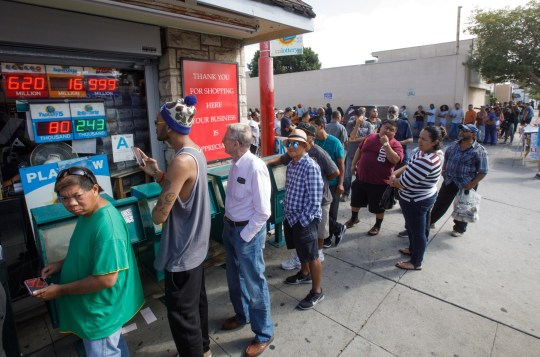 epa07114940 Hundreds of people line up to buy Mega Millions lottery tickets as the jackpot reached at least $1.6 billion outside the Bluebird Liquor store in Hawthorne, California, USA, 23 October 2018. The jackpot exceeded the store sign's ability to display more than a $999 million payout. EPA/EUGENE GARCIA