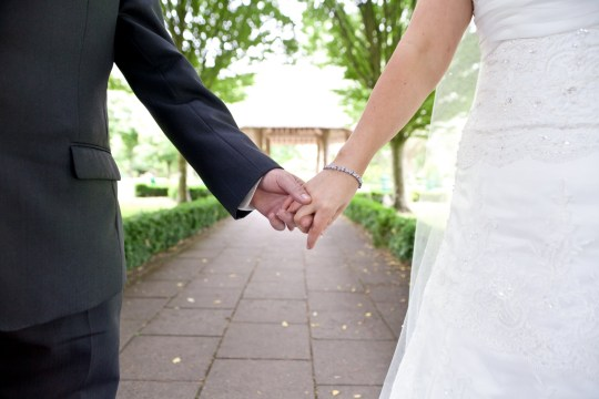 Torso level shot of a newly married couple holding hands in a park.