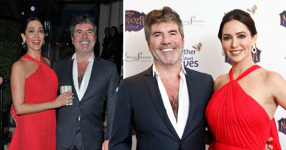 Simon Cowell looks like the cat that got the cream as he poses with Lauren Silverman at charity bash