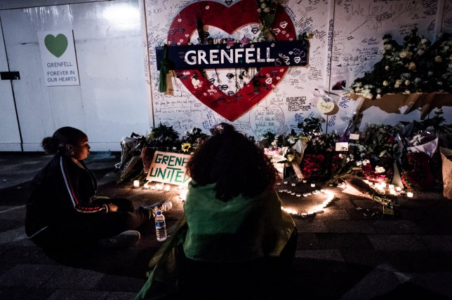 LONDON, UNITED KINGDOM - 2018/06/14: A woman seen standing in front of the flowers memorial at the foot of the Grenfell Tower. On the first anniversary of the Grenfell Tower fire, which killed 72 people, the area around the tower has been filled with flowers, candles and messages to remember those who lost their lives. (Photo by Brais G. Rouco/SOPA Images/LightRocket via Getty Images)