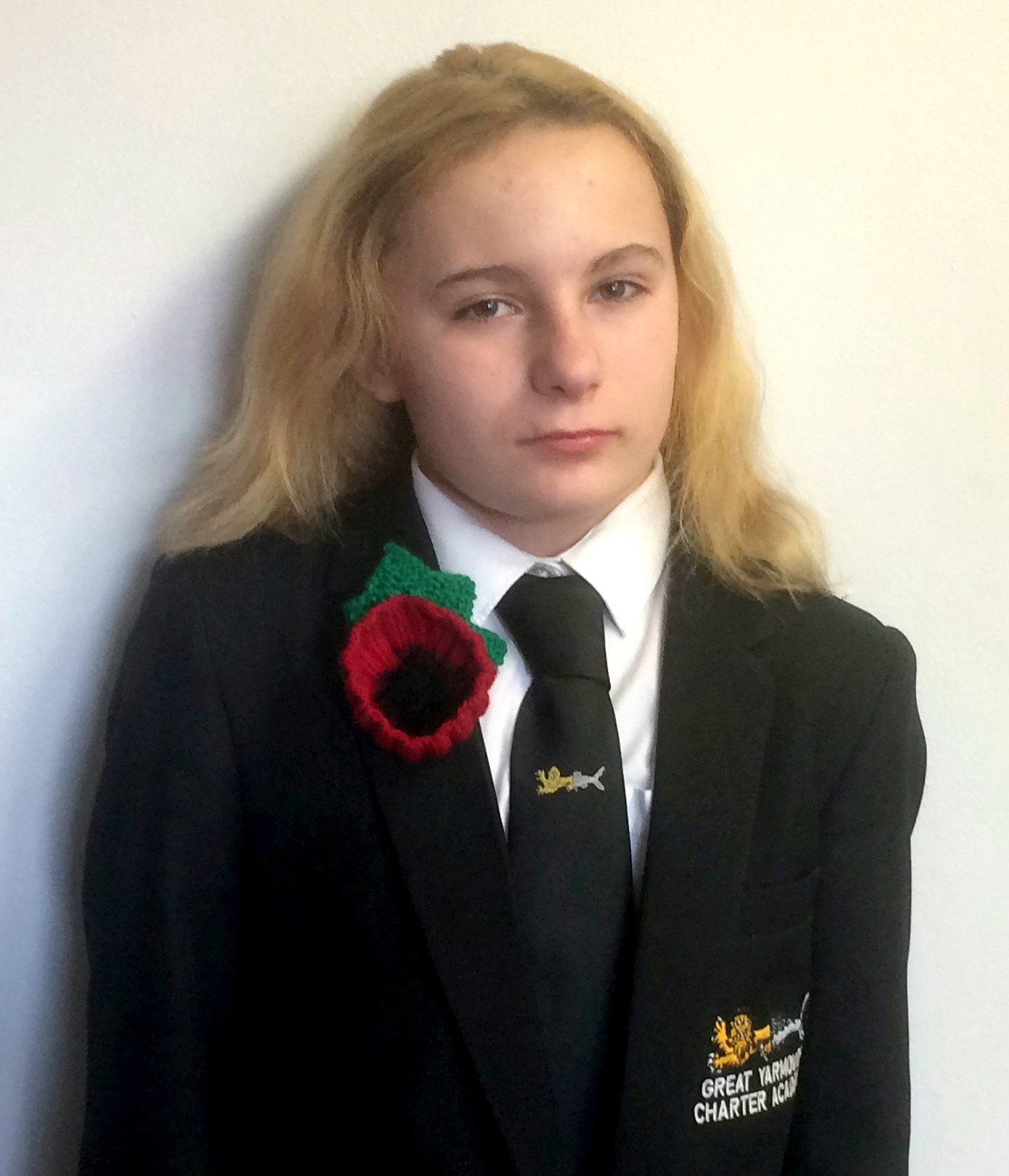 """Courtney Dougal,13, wearing the poppy she was banned from wearing at school- because it is TOO BIG!See SWNS story SWCApoppy.A teenager has been banned from wearing a knitted poppy to school - over claims it's too BIG. Courtney Dougal, 13, was told to remove the woollen symbol by teachers who said it was """"not appropriate"""" to be worn in class. The poppy is only 1cm larger than a paper version and was bought for her by her dad Raymond Dougal so she could wear it as a mark of respect for Britain's war dead. Raymond, 69, said: ?I am absolutely disgusted that they have made her take the poppy off. It doesn't make any sense."""