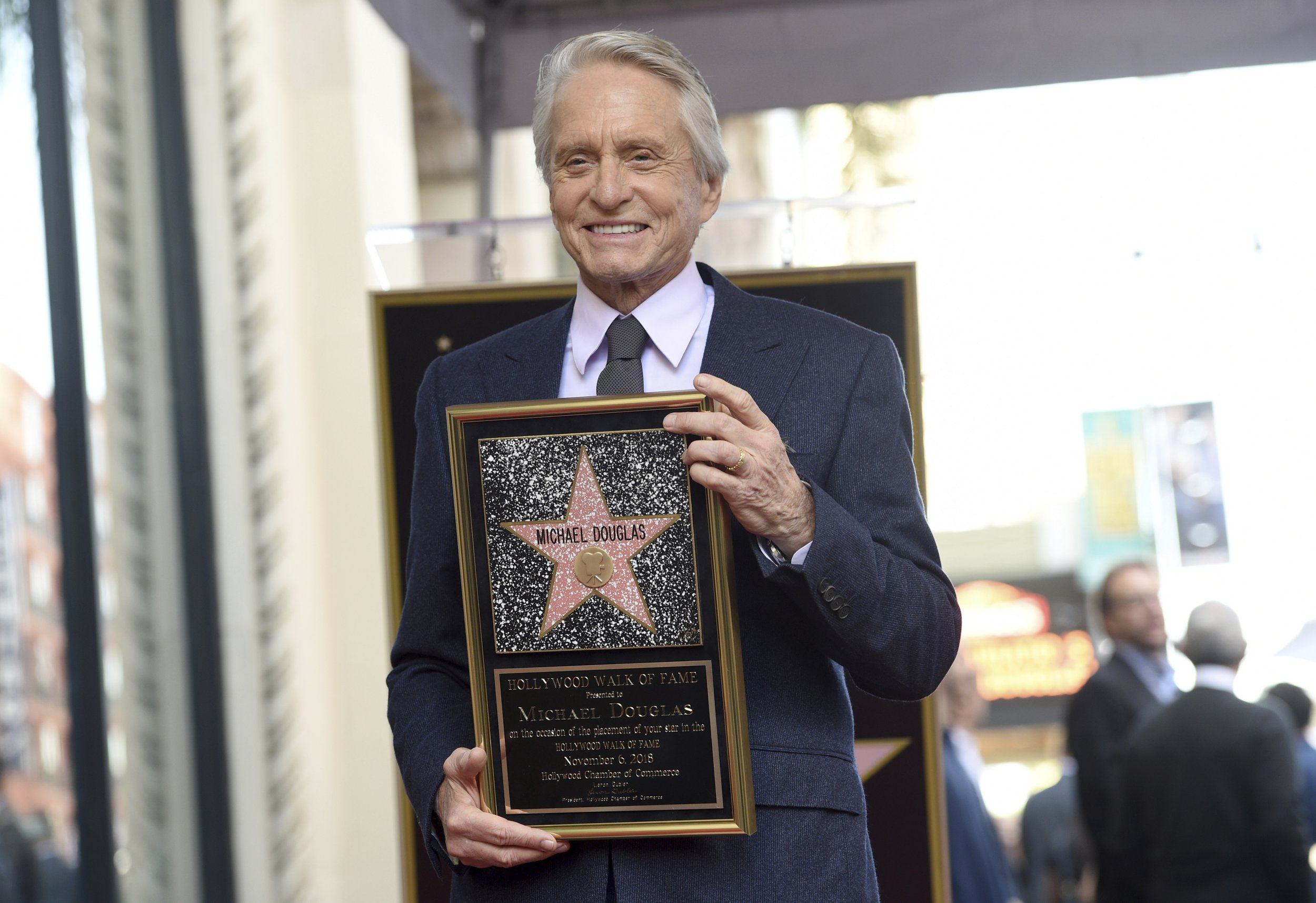 Actor Michael Douglas poses with a replica of his new star during a ceremony on the Hollywood Walk of Fame on Tuesday, Nov. 6, 2018, in Los Angeles. (Photo by Chris Pizzello/Invision/AP)
