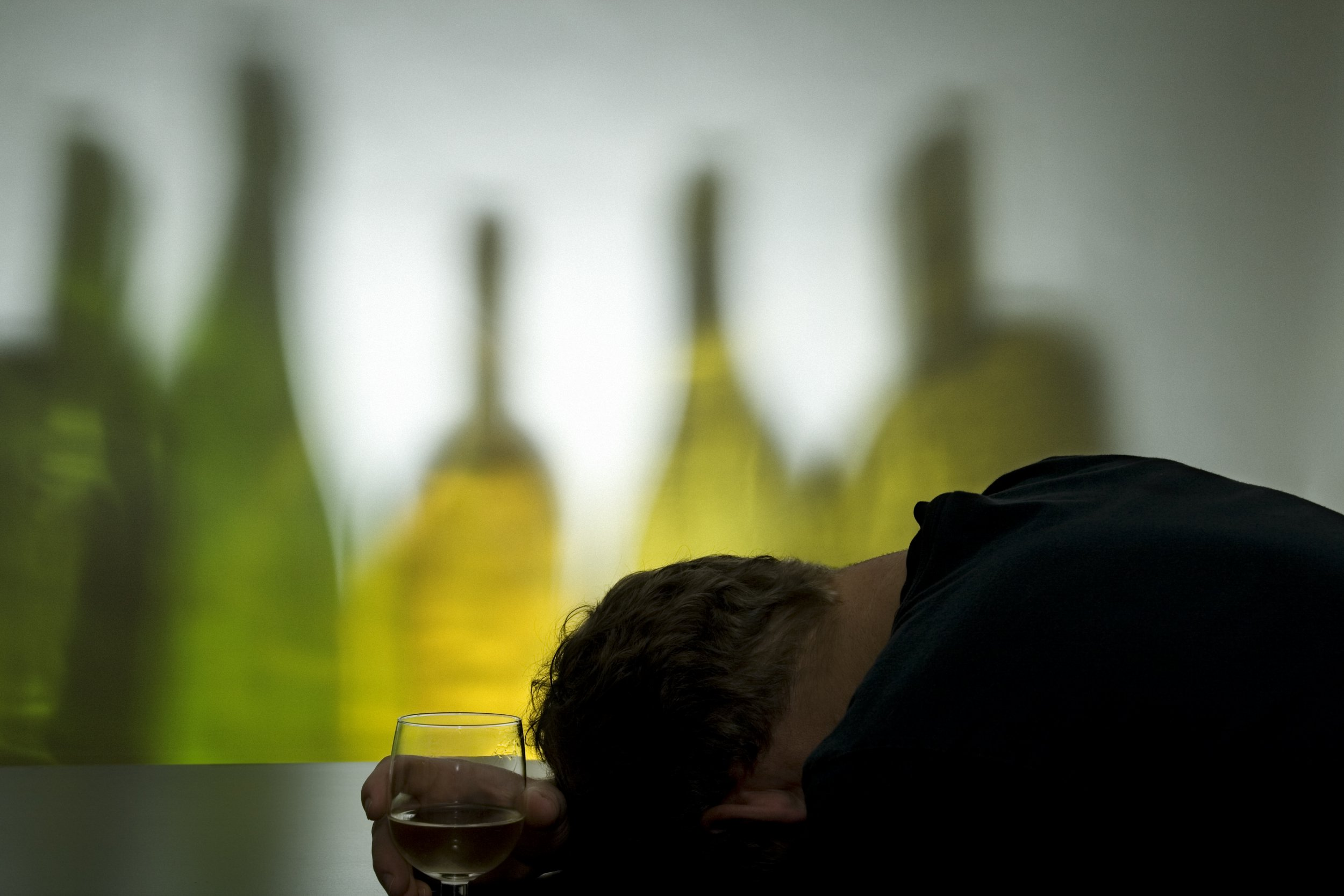Man passed out in front of wine bottles. (Light is reflected through the bottles. Noise in background.)