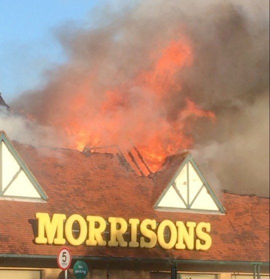 Pic by Caters News - Pictured: Firefighters were called to battle a blaze after a supermarket went up in flames and were forced to evacuate its customers before the roof eventually collapsed. Fifty firefighters were called out to Morrisons in Folkestone, Kent, at around 07:30 after a fire in the cafe kitchen spread throughout the store this morning.Kent Fire and Rescue Service said the cause of the blaze was a deep fat fryer as more specialist resources made their way to the store.The store was opened just 30 minutes before the fire started and was quickly evacuated with no reported casualties.The footage was captured by Brad Hodgkinson, a 21-year-old builder from Hawkinge, who was just metres away from the Cheriton Road store.SEE CATERS COPY.