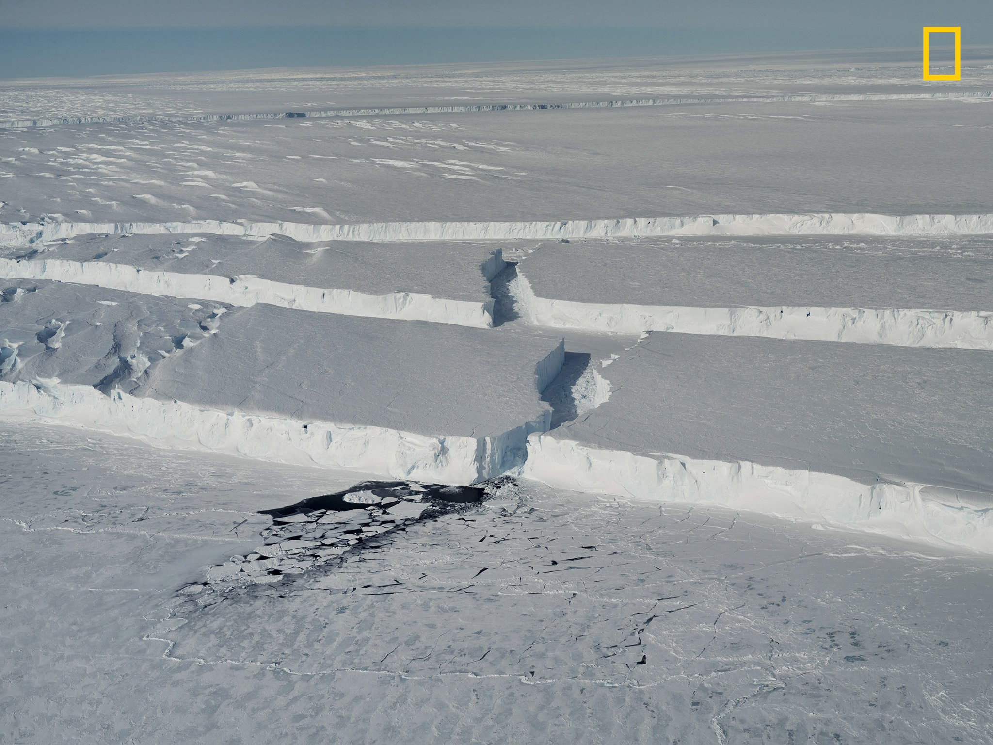 """NG News - exclusive photos: A giant iceberg breaks off Antarctica 001 Curving ice canyons mark the edge of the new iceberg, dubbed B-46, as it breaks off the thick, floating ice shelf of the Pine Island Glacier in West Antarctica. In the foreground lies broken sea ice on the dark surface of the Amundsen Sea. PERMITTED USE: This image may be downloaded or is otherwise provided at no charge for one-time use for coverage or promotion of the National Geographic article, """"Exclusive photos: A giant iceberg breaks off Antarctica"""", and exclusively in conjunction thereof. No copying, distribution or archiving permitted. Sub-licensing, sale or resale is prohibited. REQUIRED CREDIT AND CAPTION: All image uses must bear the copyright notice and be properly credited to the relevant photographer, as provided. Any uses in which the image appears without proper copyright notice, photographer credit and a caption referencing the article are subject to paid licensing Required, a link back to the original article: https://www.nationalgeographic.com/environment/2018/11/exclusive-first-pictures-of-iceberg-five-times-the-size-of-manhattan/ Images may be found here: **Branding May Not Be Removed** Mandatory Usage Requirements: You may use a Max of 2 Images online 1. Must include mandatory photo credit: Photographs by Thomas Prior / National Geographic 2. Must include prominent link back to the National Geographic story 3. Must include a mention that this is a National Geographic exclusive at the top of your piece Credit: Photographs by Thomas Prior / National Geographic"""