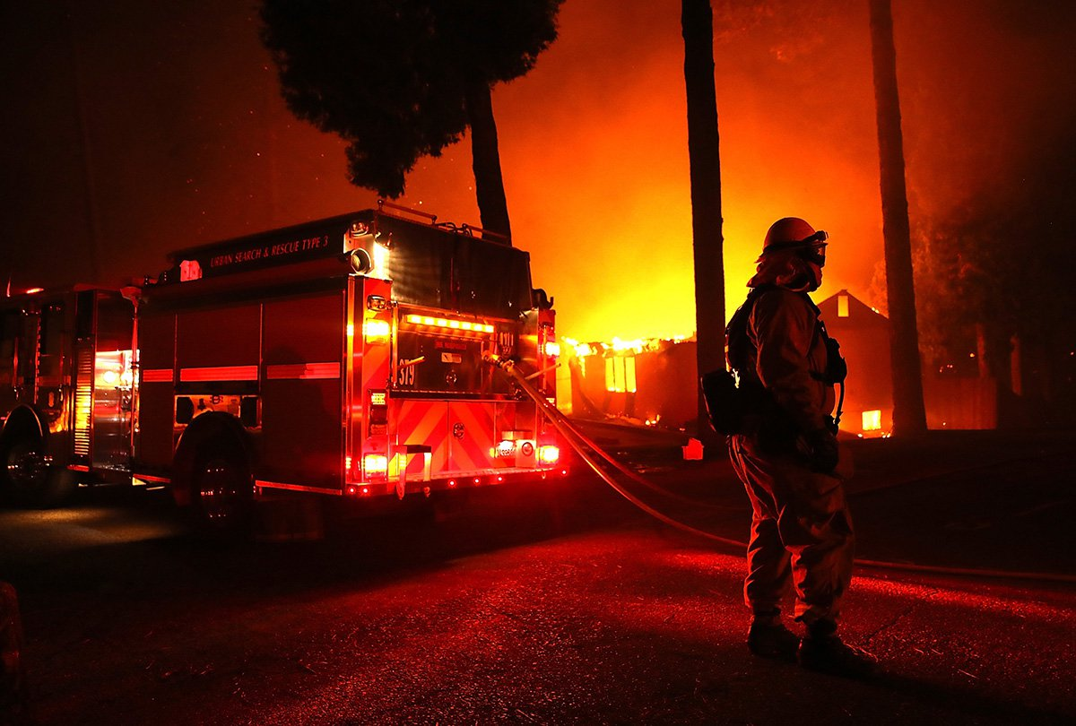 PARADISE, CA - NOVEMBER 08: Firefighters try to save a building as the Camp Fire moves through the area on November 8, 2018 in Paradise, California. Fueled by high winds and low humidity, the rapidly spreading wildfire has ripped through the town of Paradise, charring 18,000 acres and destroying dozens of homes in a matter of hours. The fire is currently at zero containment. (Photo by Justin Sullivan/Getty Images) ***BESTPIX***