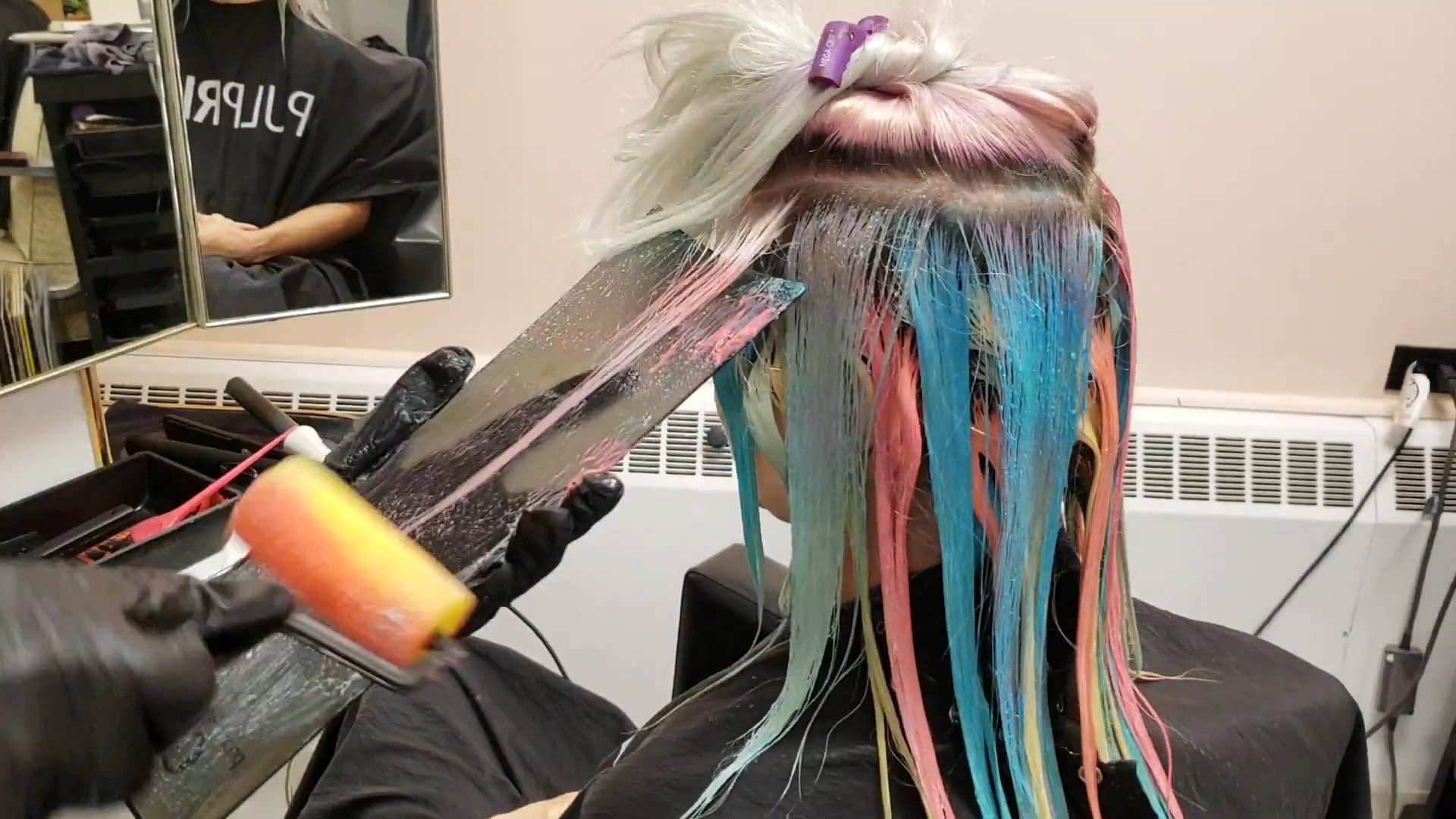 "Mesmerising footage shows a hairdresser giving a client rainbow hair using a PAINT ROLLER. See SWNS story SWNYcolor; A hairdresser who gives a client rainbow hair using a PAINT ROLLER. Kelly O'Leary, 37, created the colorful look by dipping rollers normally used for decorating into different dyes. The stylist, who runs the Sapphire Hair Lounge in Winnipeg, Manitoba, Canada, then applied the dye to strands of 32-year-old model Amanda Legris's hair. The end result is an eye-popping blend of orange, purple, pink, blue, green, red and yellow. A clip of the transformation has been watched more than 100,000 times on Instagram. Kelly, a color specialist of 20 years, said: ""I do a lot of stage shows so I am always trying to come up with new and interesting techniques. ""My model Amanda lets me use her hair a lot, and I really appreciate how she has complete faith in me. ""I just went down to our local dollar store and picked up the rollers and the trays. ""The paint rollers take up a lot of space so I wouldn?t say they are for everyday use, but it did work quite well. ""I also have tried a sponging technique which works a lot better. It is way more practical."" Kelly first tested the experimental technique during a hair exhibition in the summer. While Kelly doesn?t plan to introduce paint rollers into her salon?s daily routine, the hair stylist said she would be happy to pull them out for anyone who asked in advance. Kelly said: ""When I put it on Instagram, everyone was really excited. ""If someone wrote to me and asked, I definitely would be down for doing it. I?d just have to be prepared in advance."